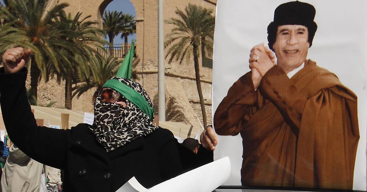 A supporter of Libyan leader Muammar Gaddafi shouts slogans next to his picture while taking part in a pro-government rally in Tripoli on Feb. 17, 2011.</p>