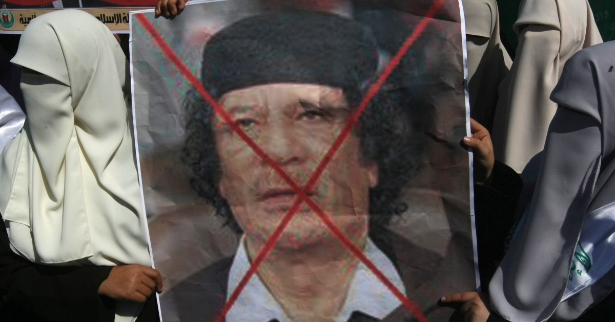 Palestinian students attend a protest against Libyan leader Muammar Gaddafi (portrait) in Gaza City on Feb. 22, 2011. Gaza's Hamas rulers heaped condemnation on 'the massacres' of anti-government protestors in Libya.</p>