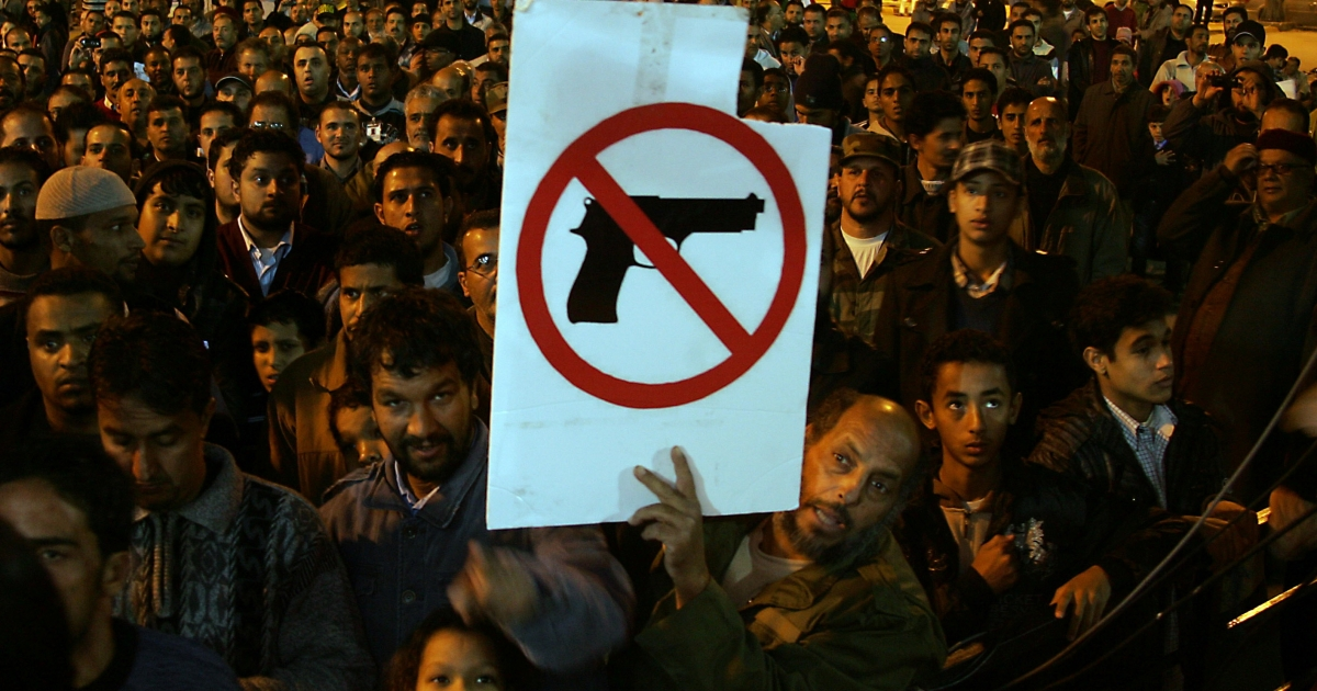 A Libyan demonstrator holds a sign as people gather for a protest calling for the disarming of militiamen in the eastern city of Benghazi on Dec. 13, 2011.</p>