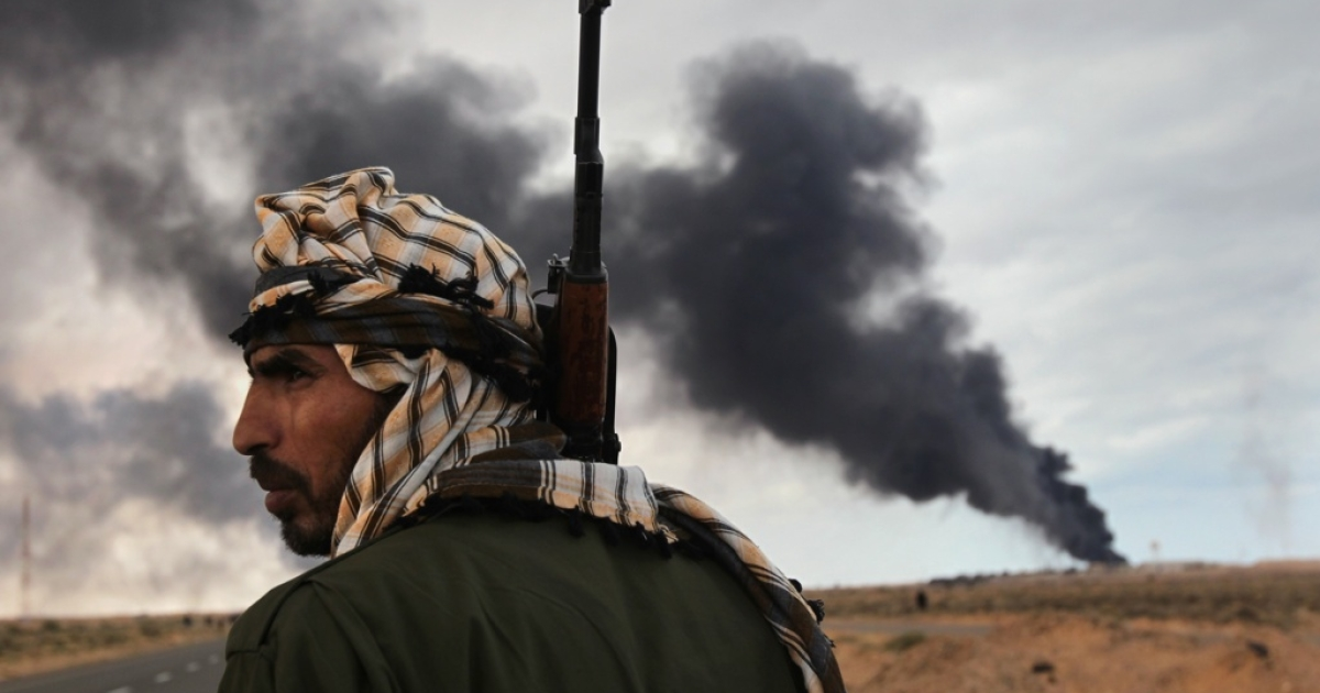 A Libyan rebel scans the horizon as an oil facility burns on March 9, 2011 near Ras Lanuf, Libya. The rebels pushed back government troops loyal to Libyan leader Muammar Gaddafi towards Ben Jawat.</p>