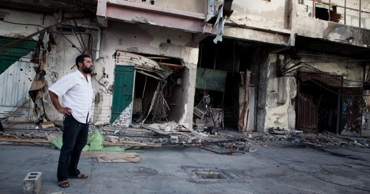 A local resident stands in front of his war-torn apartment building in Misrata, Libya on Sept. 3, 2011.</p>