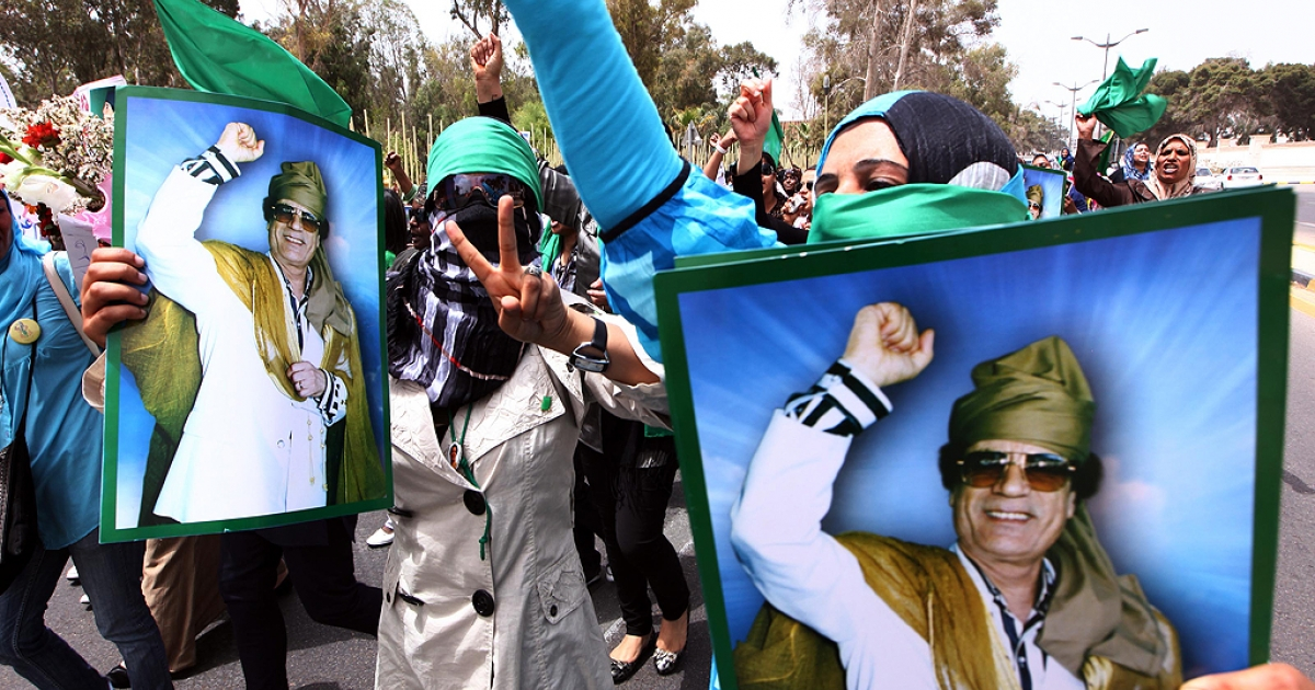 Libyan women hold pictures of Libyan leader Moamer Kadhafi as they rally outside the Rixos Hotel where foreign journalists are based in the Libyan capital Tripoli on May 22, 2011 in Tripoli.</p>