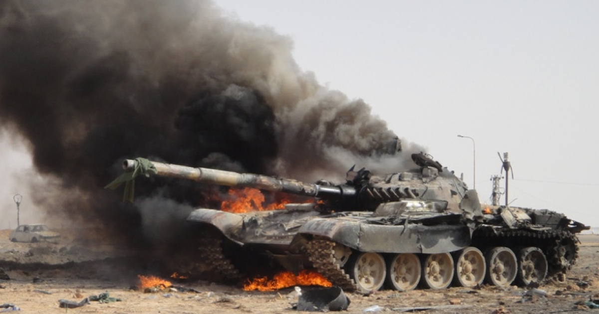 A tank belonging to forces loyal to Libyan leader Muammar Gaddafi smolders outside the gates of Ajdabiya after an allied air strike on March 26, 2011.</p>