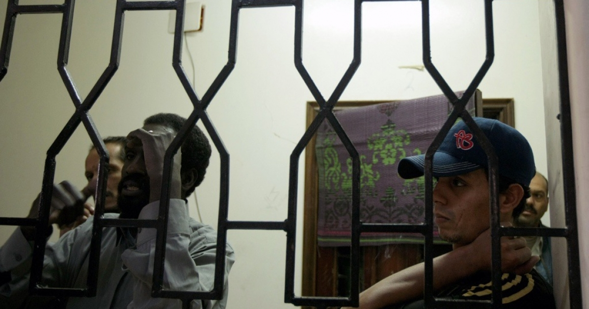 Libyan prisoners stand behind bars at the rebel's military jail in the eastern town of Benghazi on April 20, 2011.</p>