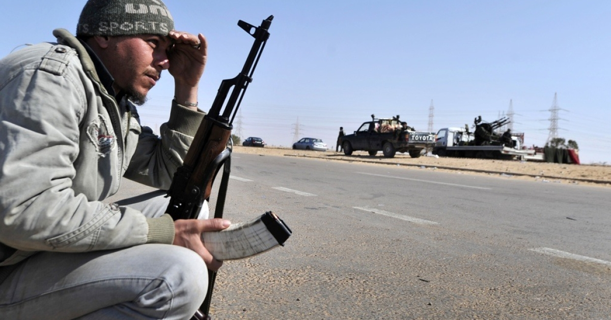 A Libyan rebel crouches at the last check point before the key city of Ajdabiya on March 23, 2011. Government forces have encircled the town.</p>