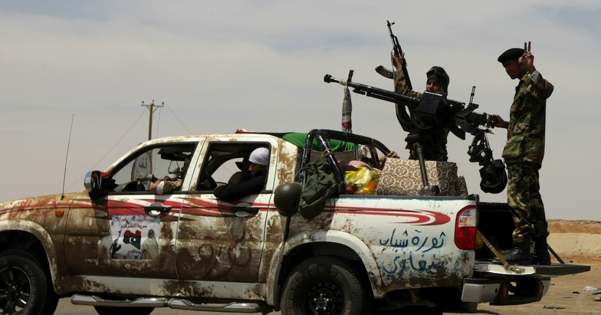 Libyan rebels drive to the battle front line between the strategic town of Ajdabiya and the town of Brega, on April 21, 2011.</p>