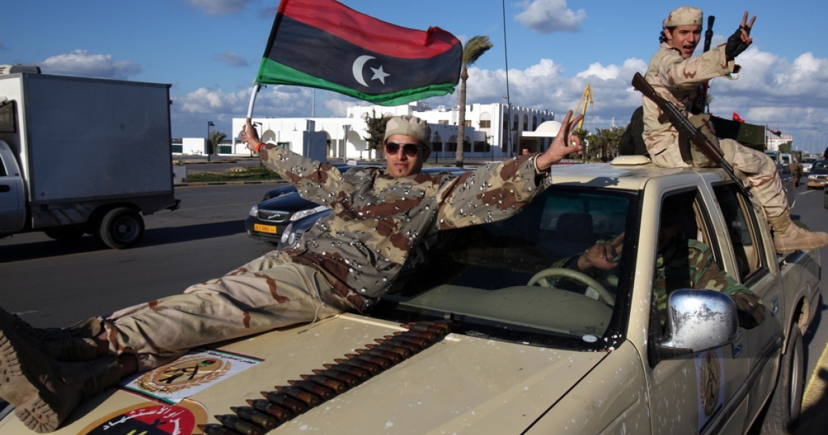 Libya's former rebels, who have now joined the new Libyan army, wave Libya's new flag as they parade through Tripoli on Feb. 14, 2012.</p>