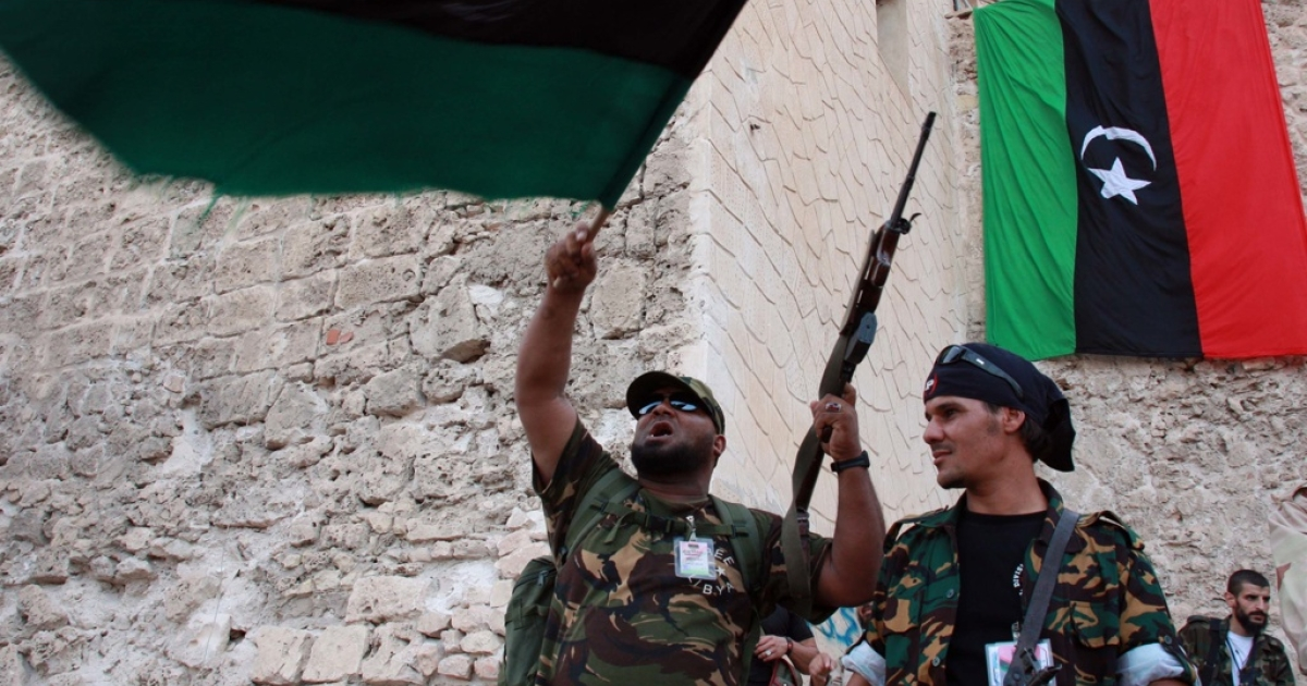 Libyan rebels from the National Transitional Council wave the newly adopted Libyan flag in Martyr's Square in the capital Tripoli during a rally on the third on September 2, 2011.</p>