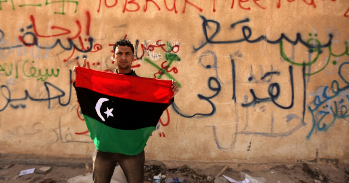 A Libyan anti-government protester holds his old national flag in front of a wall covered with graffiti against Libyan leader Muammar Gaddafi in the eastern city of Tobruk on Feb. 24, 2011.</p>