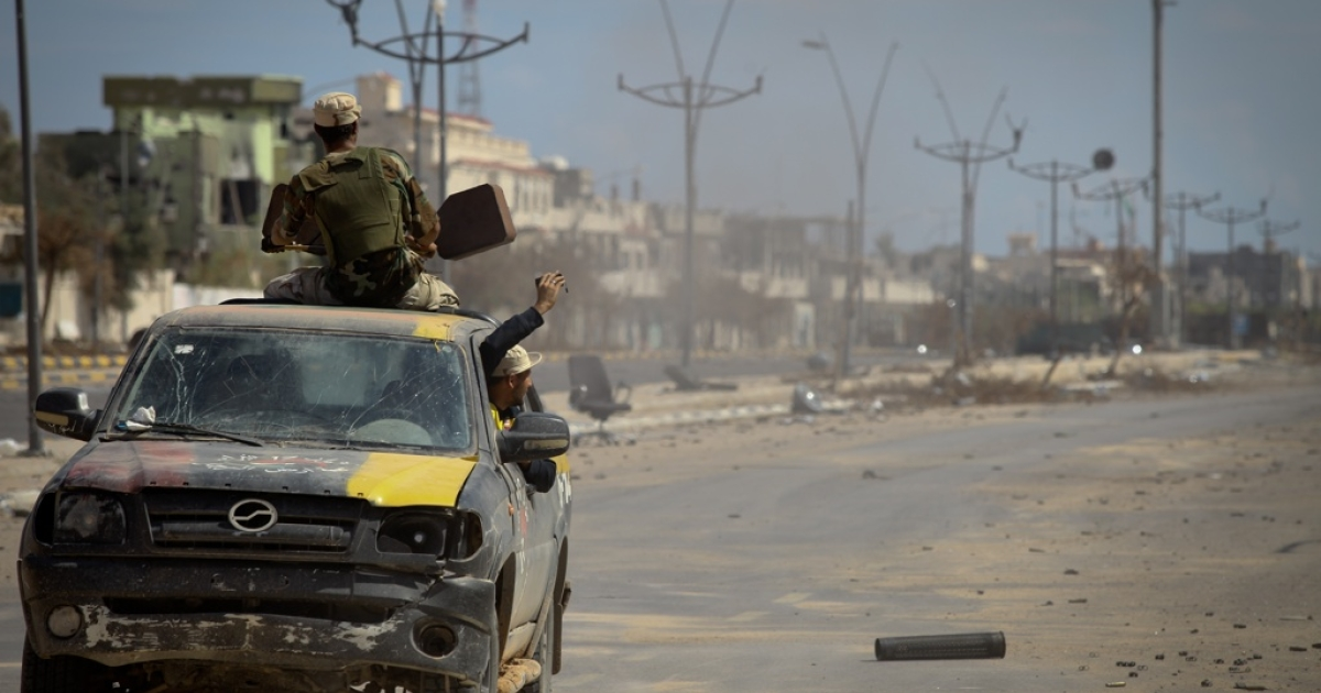 A Libyan fighter shoots an anti-aircraft gun while the driver, who is also driving, films the action.</p>