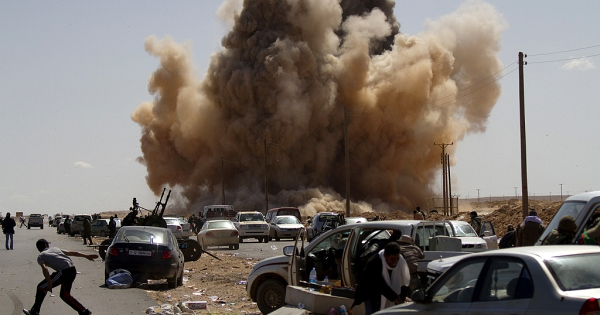 Libyan rebel fighters take cover as a bomb dropped by an airforce fighter jet explodes near a checkpoint on the outskirts of the oil town of Ras Lanuf on March 7, 2011.</p>