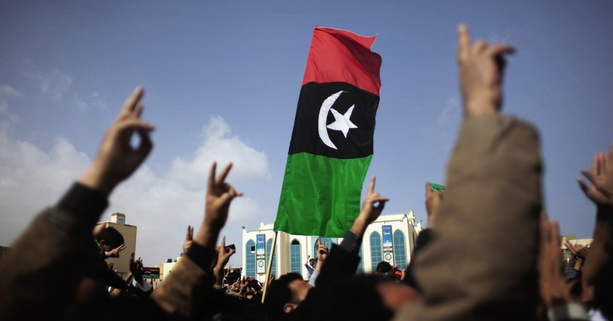 Libya's old national flag flutters as anti-government demonstrators gather for a protest in the eastern Libyan city of Tobruk on Feb. 25, 2011.</p>