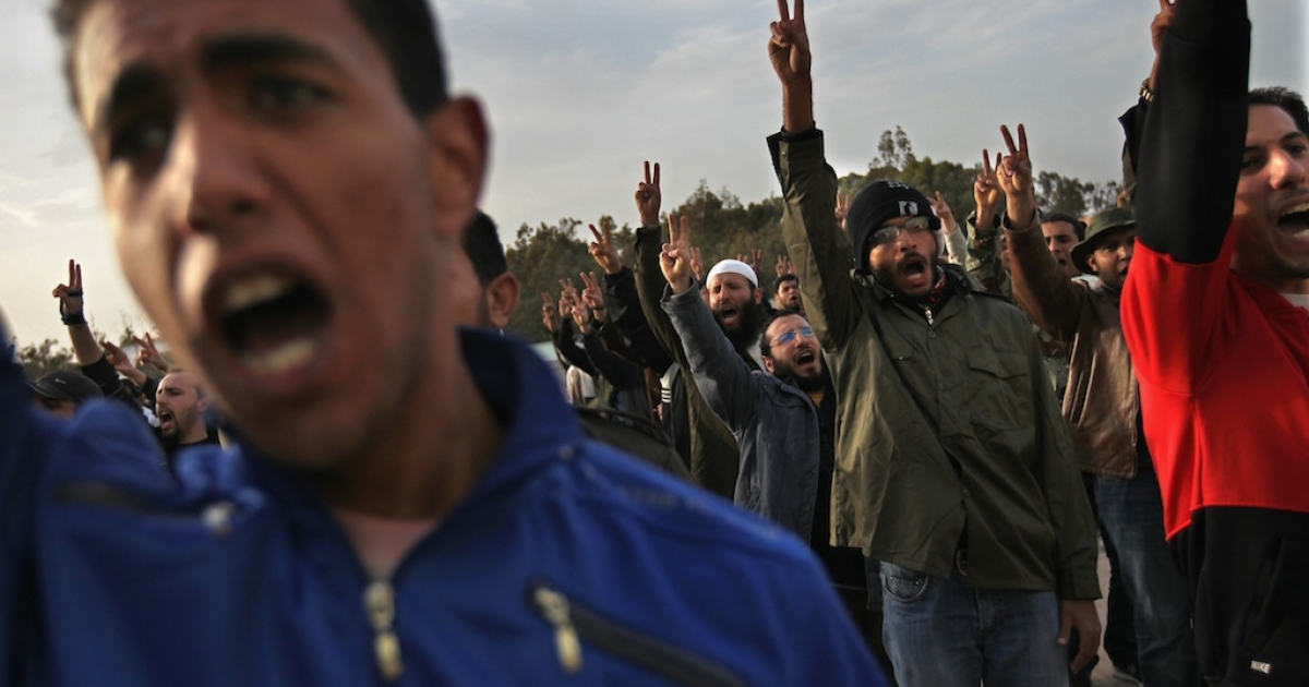 Rebel volunteers cheer on their first day of military training at a rebel militia center on March 1, 2011, in Benghazi, Libya.</p>