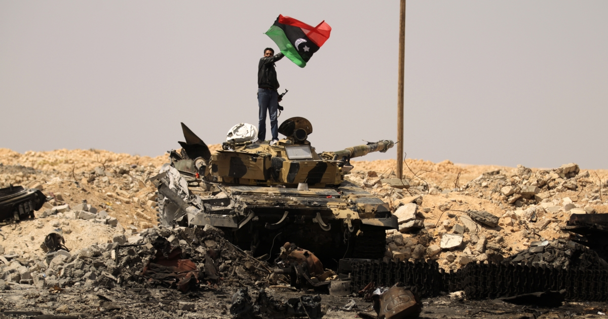 A Libyan rebel waves the rebellion flag on a loyalist army tank at a site bombed by coalition air force in the town of Ajdabiya on March 26, 2011 as forces loyal to Libyan leader Muammar Gaddafi were retreating after rebels recaptured the key eastern town in their first significant victory since the launch of the Western-led air strikes a week ago.</p>