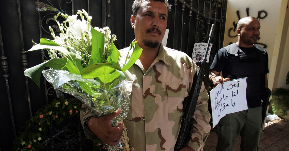 Libyan security guards hold flowers and slogans left by people protesting against last week's attack, in which ambassador Chris Stevens died, at the main entrance of the US consulate in Benghazi. Around 30,000 Libyans joined a rally in Benghazi on September 21, 2012, protesting the powerful militias that have run rampant in the country.</p>