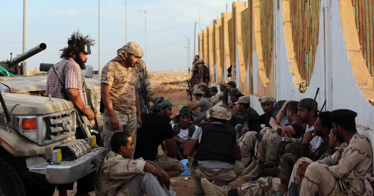 Pro-government forces gather to rest against a wall on October 21, 2012, some three kilometers from the northern entrance to the Bani Walid, one of the final bastions of Muammar Gaddafi's regime.</p>