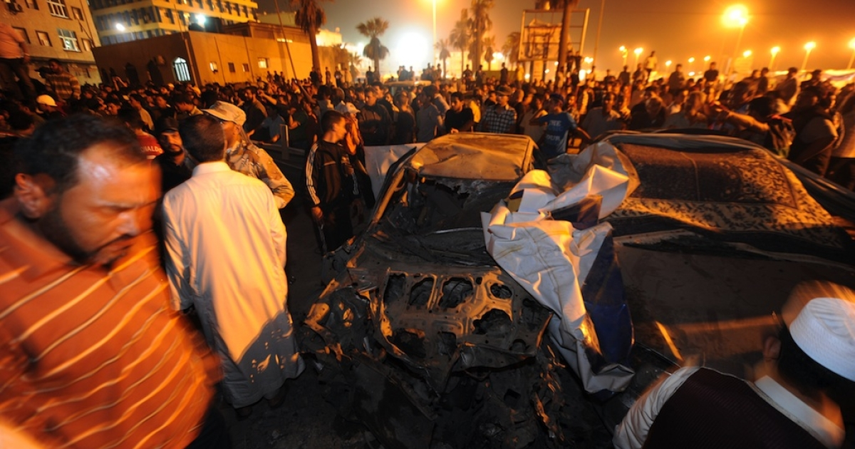 People gather around the remains of car which exploded near the headquarters of Libya's rebels in their eastern bastion of Benghazi late on May 3, 2011.</p>