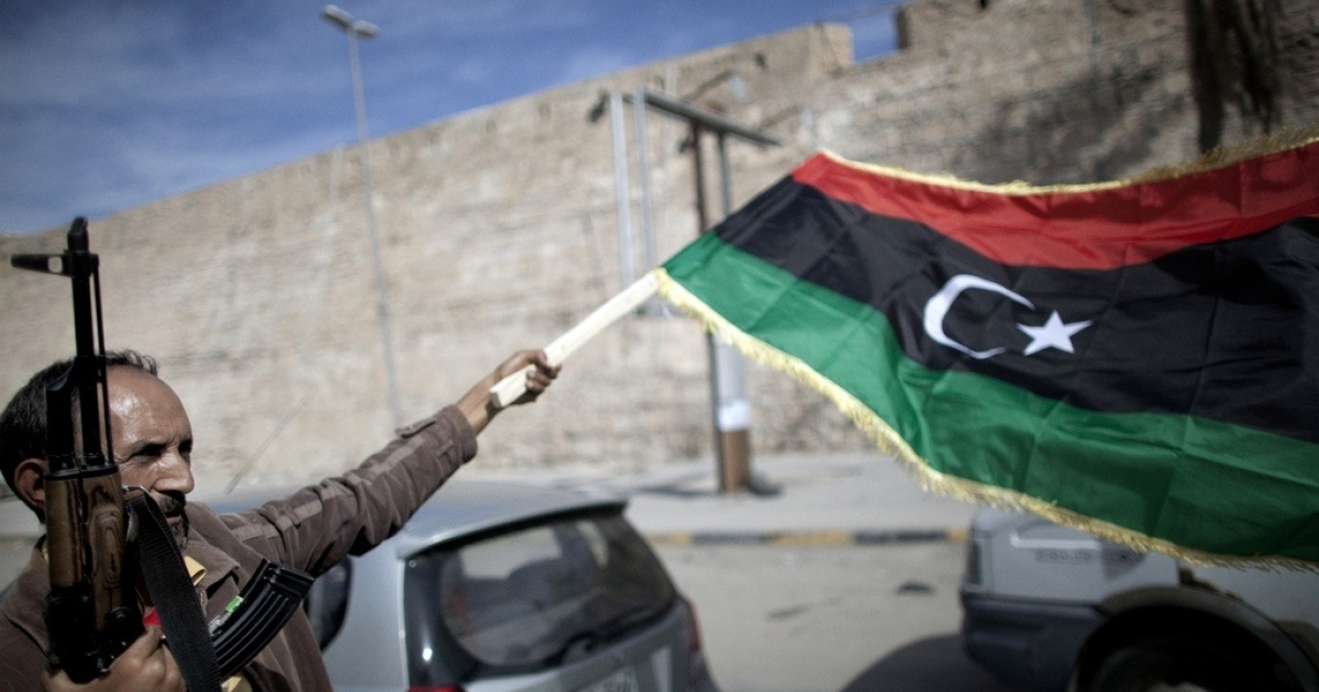 A Libyan fighter waves the new government's flag after the reported death of Gaddafi.</p>