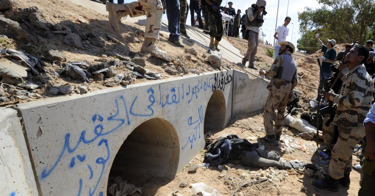 Libyan National Transitional Council (NTC) fighters stand outside drainage pipes where ousted Libyan leader Muammar Gaddafi was captured, as the body of a loyalist lies on the ground, in the coastal Libyan city of Sirte on October 20, 2011.</p>