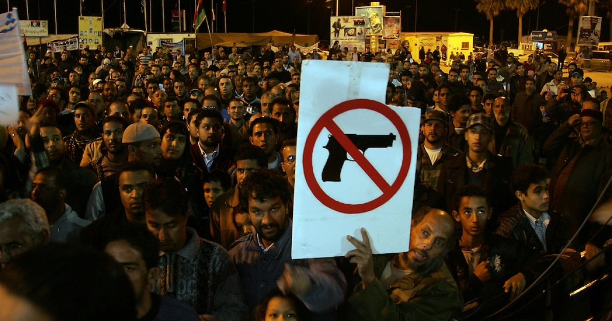 A Libyan demonstrator holds a sign as people gather for a protest calling for uniting the army and disarming militiamen in the eastern city of Benghazi on December 13, 2011. AFP PHOTO/ABDULLAH DOMA</p>