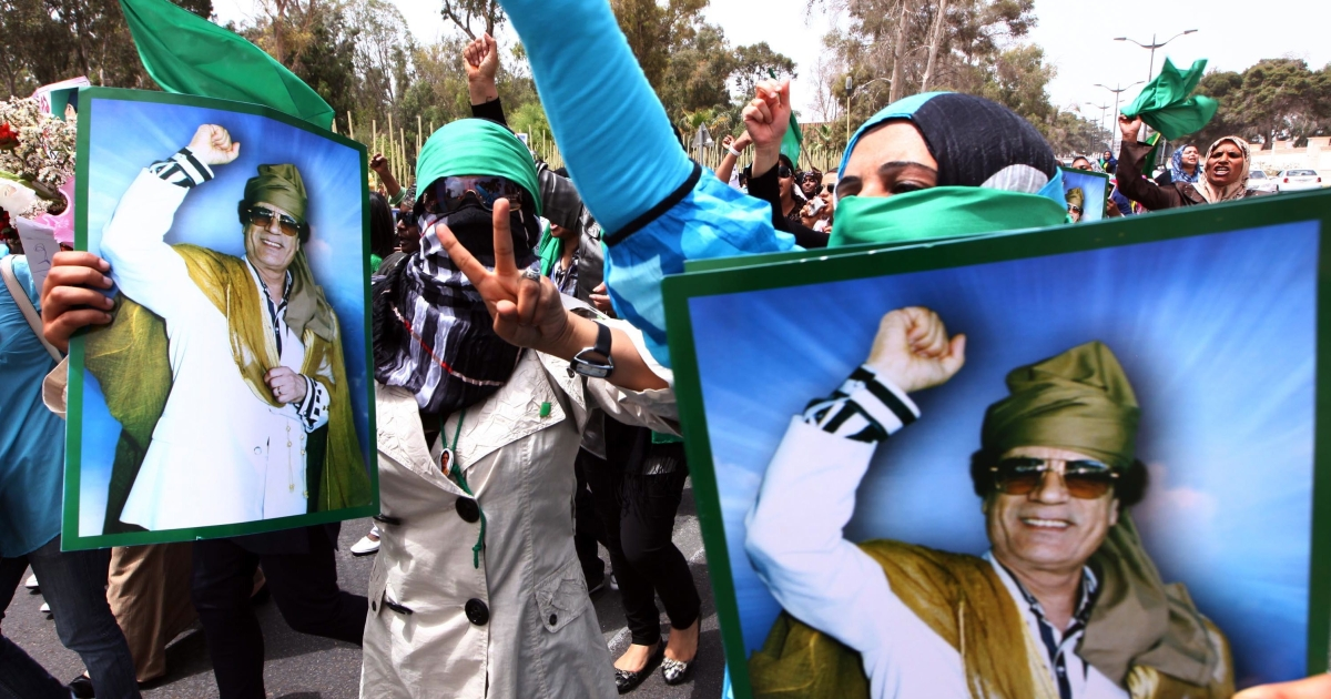 Libyan women hold pictures of Libyan leader Muammar Gaddafi as they rally outside the Rixos Hotel where foreign journalists are based in the Libyan capital Tripoli on May 22, 2011 in Tripoli.</p>