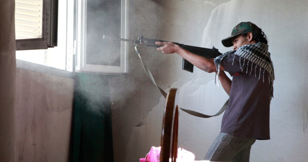 Mohammed Al Derbale, 19, fires an FN rifle at Gaddafi troops from the window of an abandoned farmhouse in Dafnia.</p>