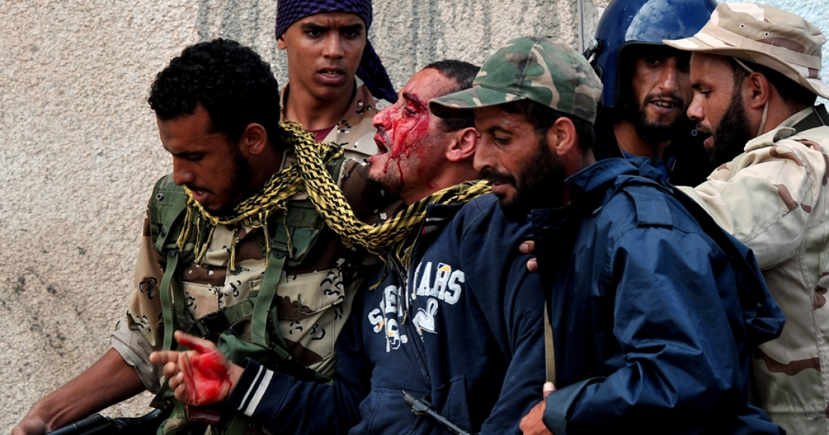 Libya's new regime forces capture a fighter loyal to fugitive strongman Muammar Gaddafi during a battle in Sirte on October 10, 2011, in a drive to control Gaddafi's hometown after a month-long siege.</p>