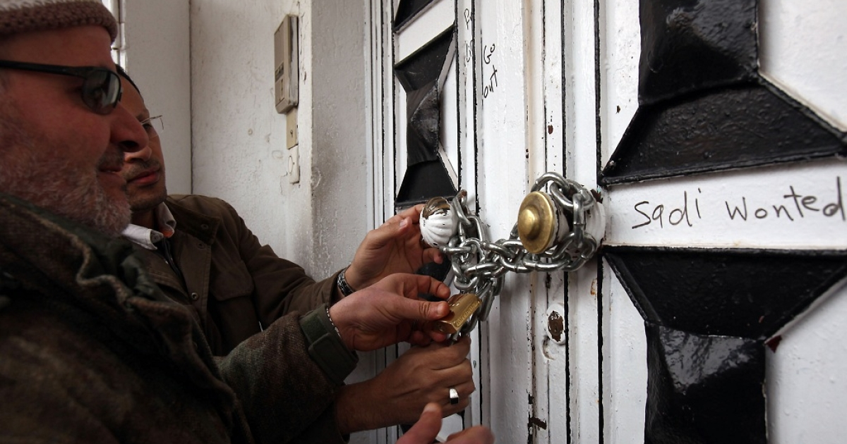 Libyan protesters lock the door of the Niger embassy with a chain during a demonstration in Tripoli over the neighbouring country's refusal to hand over Saadi Kadhafi. Niger will not extradite Saadi Kadhafi even though the son of the slain Libyan leader violated his asylum conditions with 'subversive' comments in a television interview, officials said.</p>