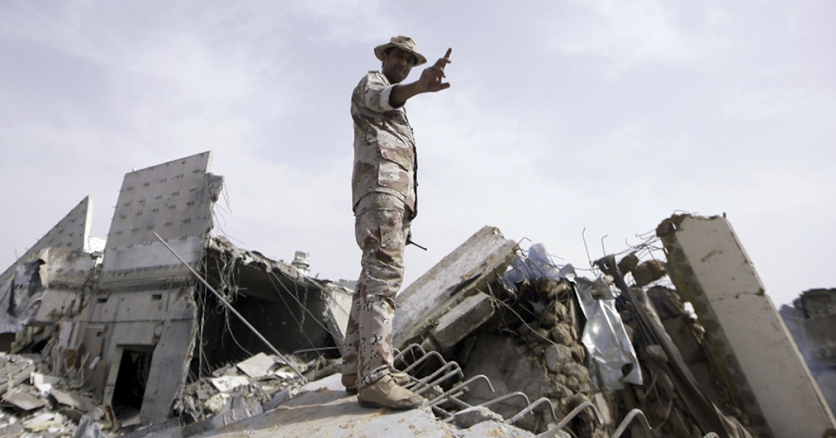 A Libyan soldier stands on top of a destroyed building in the Bab Al-Aziziya district of Tripoli on June 7, 2011 after NATO warplanes pounded the Libyan capital. Libya has accused NATO of killing at least five civilians in an air strike that hit a house in Tripoli in the early morning of June 19, 2011.</p>