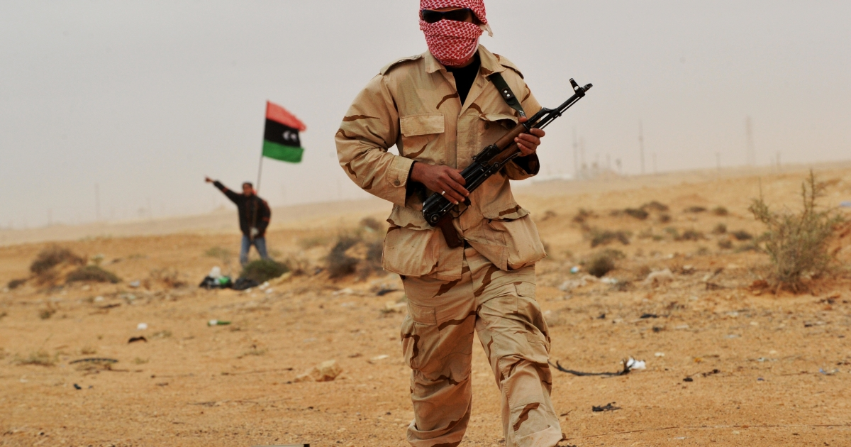 A rebel fighter walks toward clashes between pro-Gaddafi forces and rebels on the outskirts of the north-central Libyan town of Bin Jawad on March 8, 2011.</p>