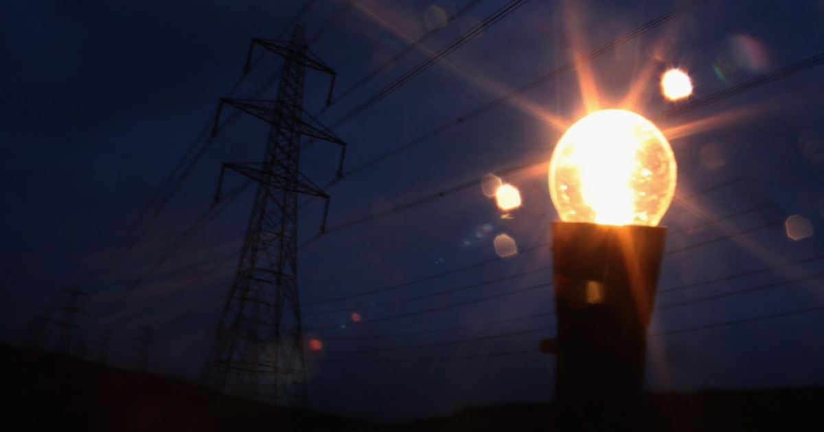 An incandescent light bulb is illuminated next to electricity pylons.</p>