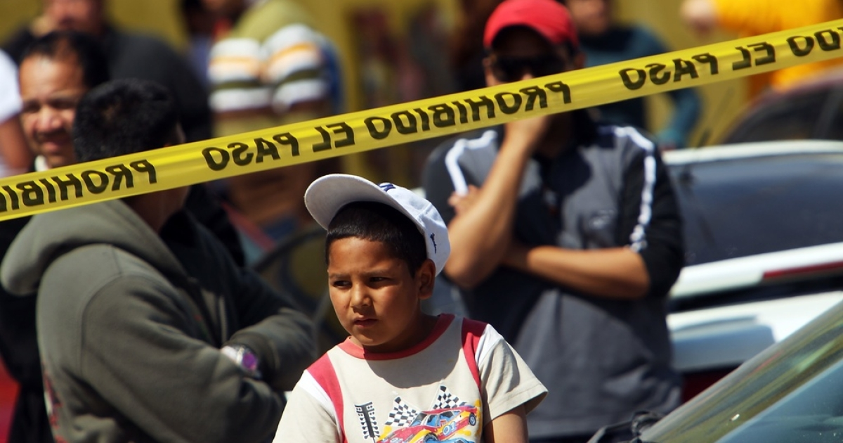In Texas, children as young as 11 have been pulled into the trade. Here, a little boy looks over a crime scene in the Mexican border town of Ciudad Juarez.</p>