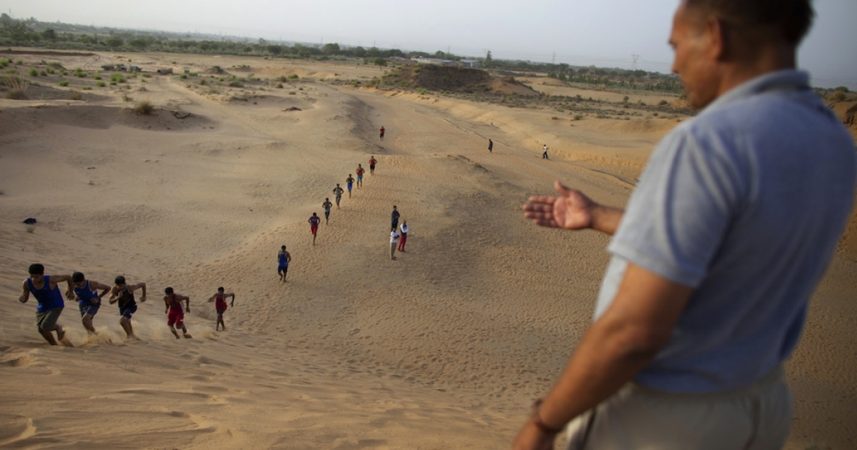 This photo taken on June 12, 2012 shows Indian boxers from the Bhiwani Boxing Club (BBC), dubbed the 'Little Cuba', running up a sand dune towards coach Jagdish Singh (R) during an early morning desert training session in Bhiwani.</p>