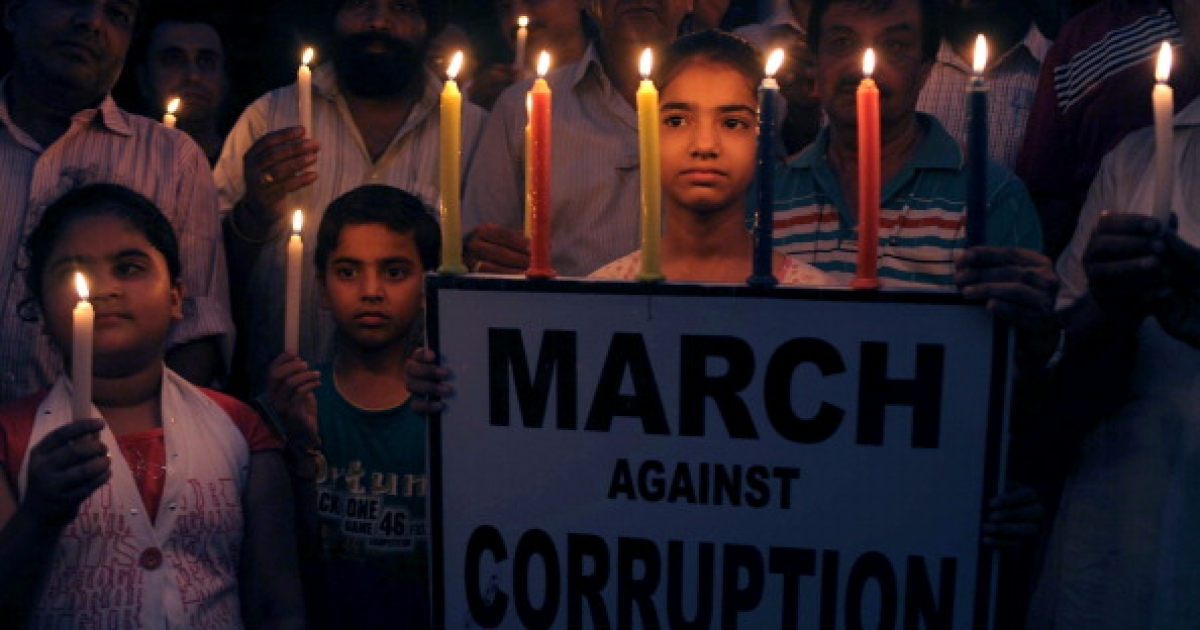 Supporters of anti-corruption activist Anna Hazare hold placards and candles during a protest against corruption in Amritsar on August 23, 2011.</p>