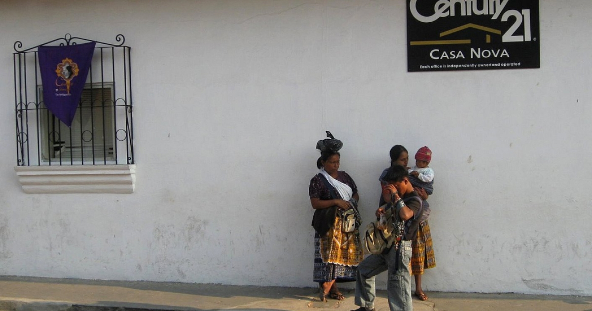 Some indigenous women stand in front of a sign for a realtor company in Antigua, Guatemala. Women in Guatemala face high murder rates, although homicides declined in 2012.</p>