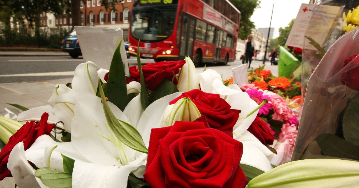 A bus passes floral tributes placed next to a memorial remembering the victims of the 7/7 terrorist attacks in London.</p>