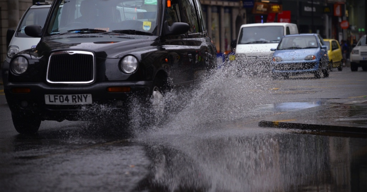 A black cab drives through a puddle in central London on June 11, 2012.</p>