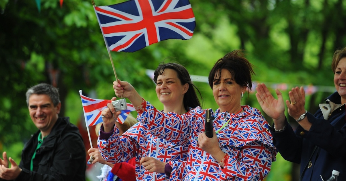 Spectators dressed in the Union Flag cheer on the Olympic Flame on the Torch Relay leg between Burnley and Rawtenstall in England.</p>