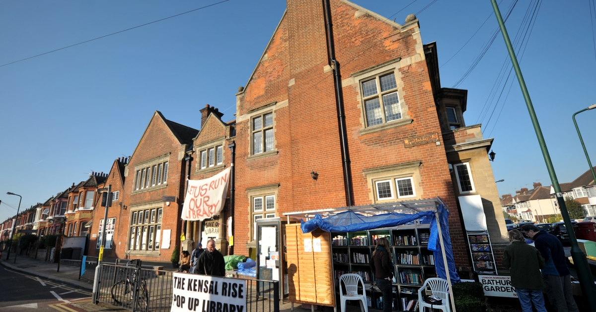 Banners hang outside the closed Kensal Rise Library as people pass by the