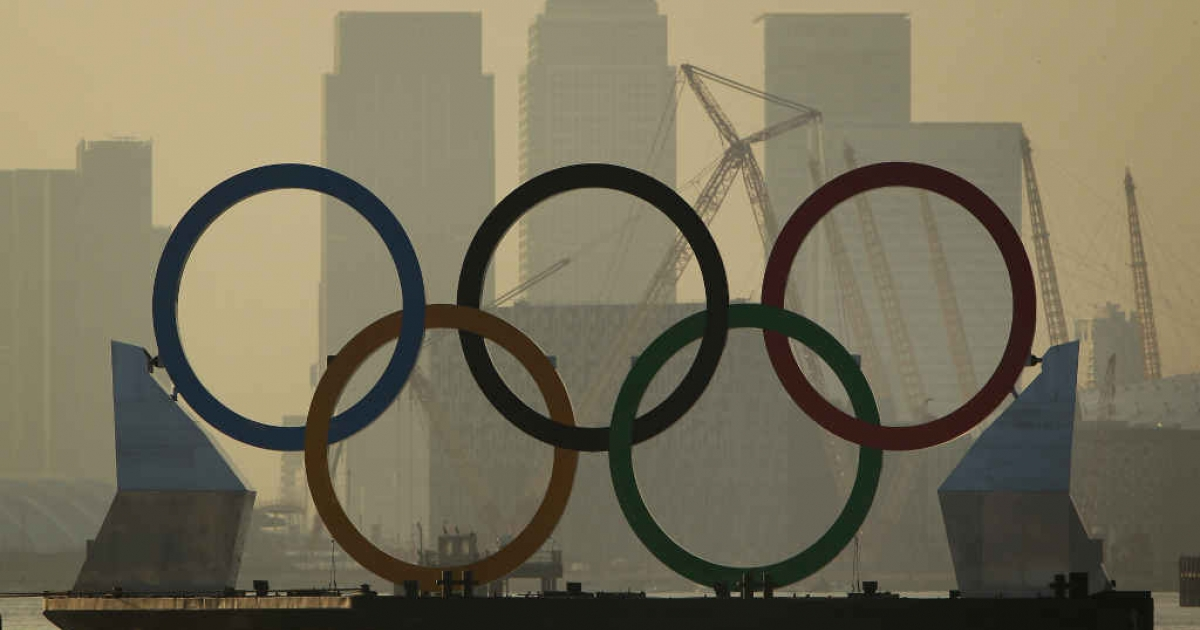 Giant Olympic rings are towed on the River Thames in London, England.</p>