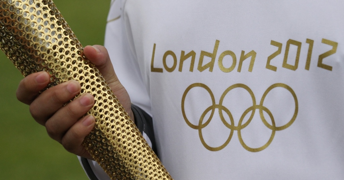 An Olympic 'torch bearer' holds a London 2012 Olympic torch in Kew Gardens on April 18, 2012 in London, England.</p>