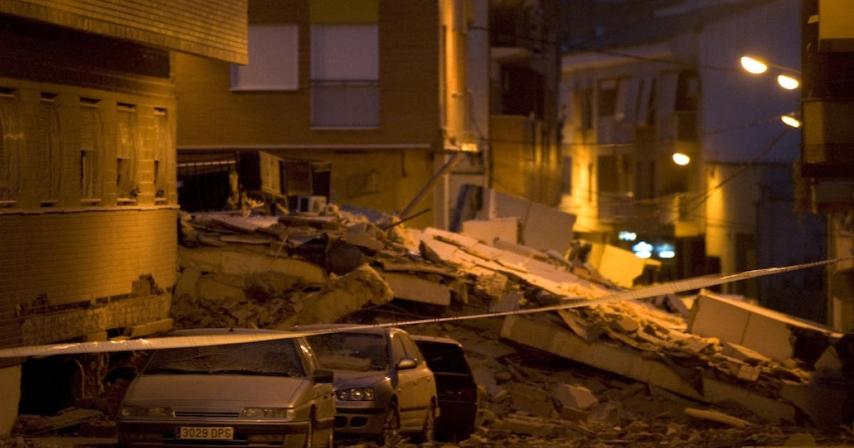 View of cars crashed by debris from a collapsed building in Lorca, Spain, on May 11, 2011, after an earthquake killed at least 10 people.</p>