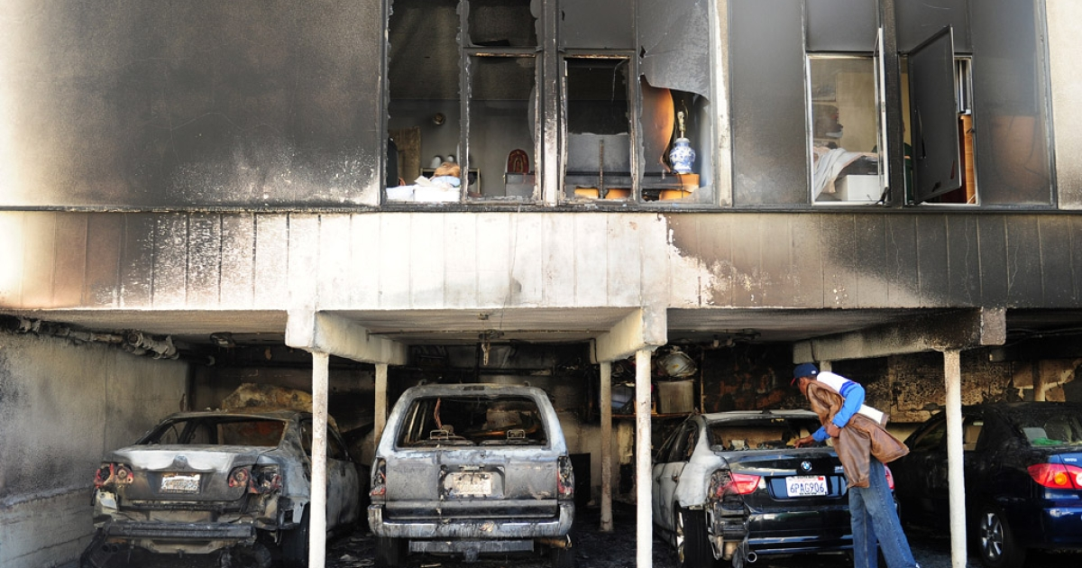 A passerby inspects damaged cars following an overnight fire started by a suspected serial arsonist in Hollywood, California. 35 fires have been reported in the past two days.</p>