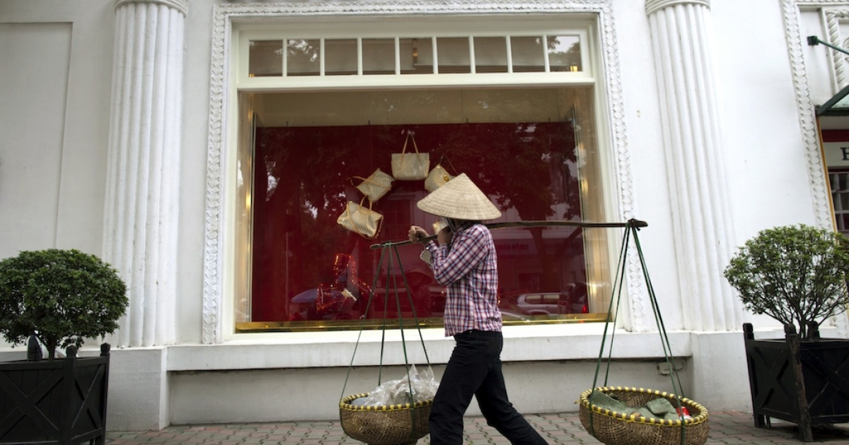 A Vietnamese woman walks by the Louis Vuitton shop in the French quarter in Hanoi, Vietnam.</p>