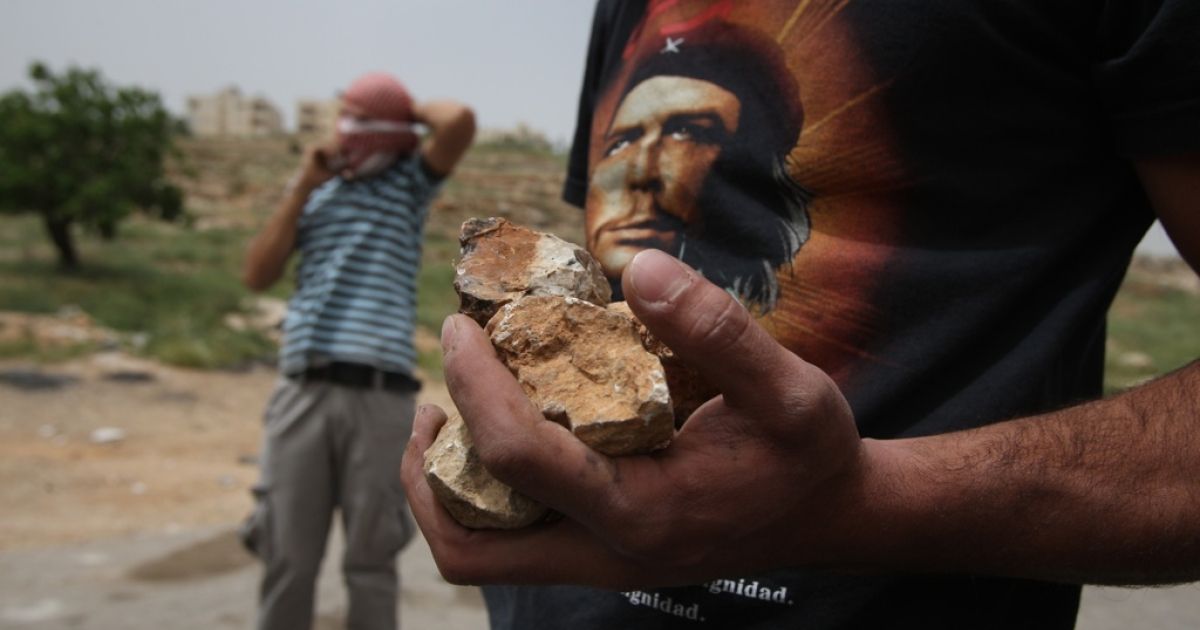 A Palestinian protester, wearing a t-shirt bearing a portrait of Che Guevara, carries stones during clashes with Israeli troops outside Ofer military prison near the West Bank city of Ramallah on May 1, 2012.</p>