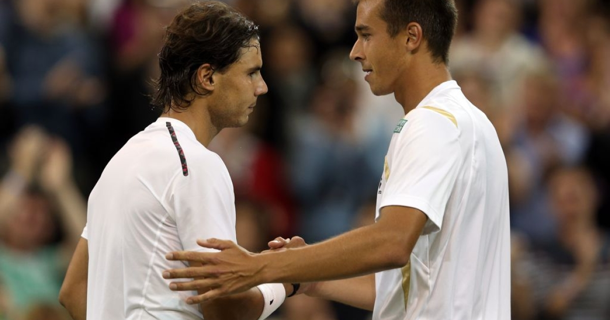 Lukas Rosol of the Czech Republic (R) shakes hands with Rafael Nadal of Spain after sending him out of Wimbledon on day four.</p>