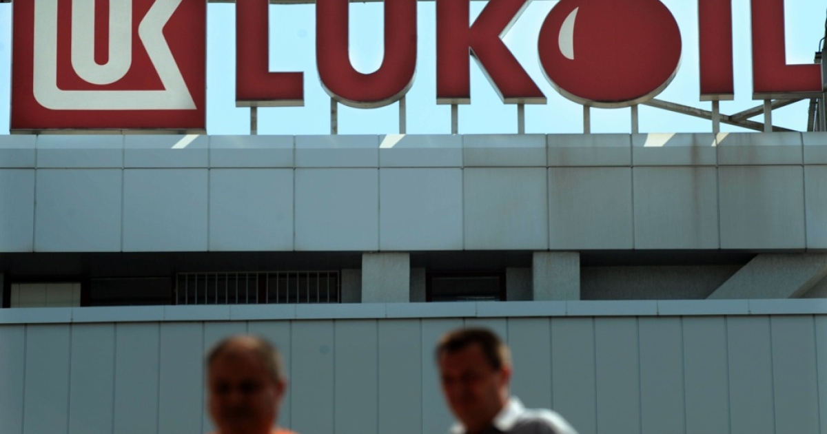 People walk by the Lukoil Neftochim Headquarters in Sofia on July 27, 2011.</p>
