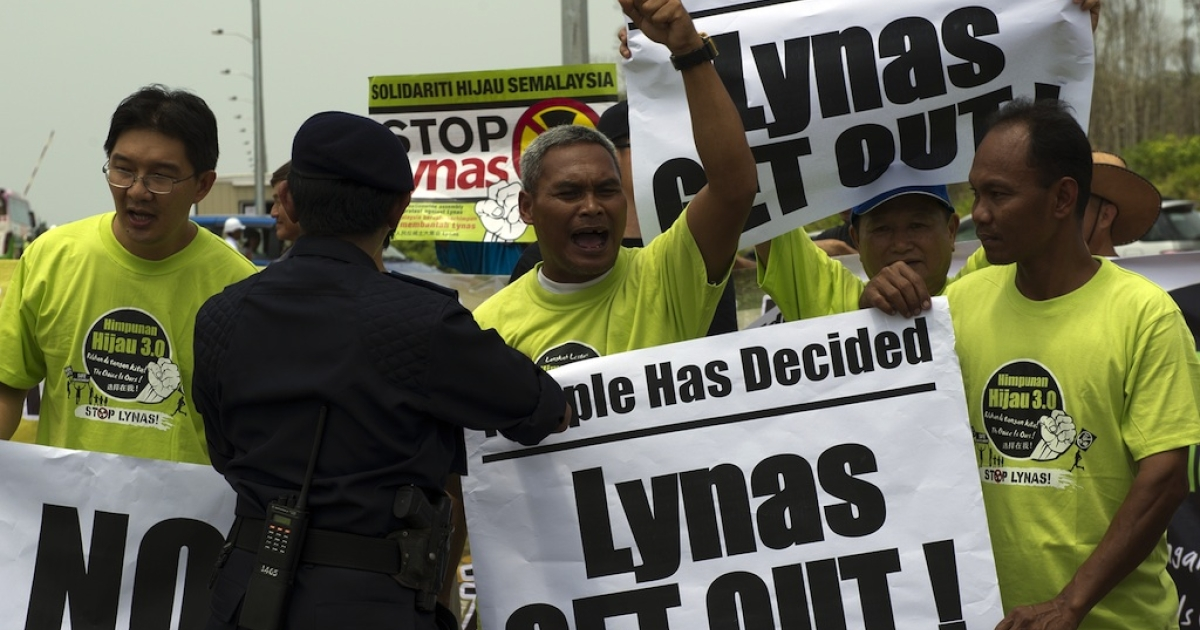 A Malaysian police officer asks anti-Lynas activists to move off the road as they protest against the Lynas Corporation near the under construction Lynas plant in Gebeng, some 270 kilometers east of Kuala Lumpur on April 19, 2012. Scores of anti-lynas activists gathered to record their protest during a media tour to the plant. The Australian miner Lynas Corporation will process rare earths imported from the Mount Weld mine in Western Australia.</p>