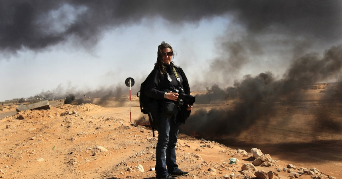 American photojournalist Lynsey Addario stands near the frontline during a pause in the fighting on March 11, 2011 in Ras Lanuf, Libya.</p>