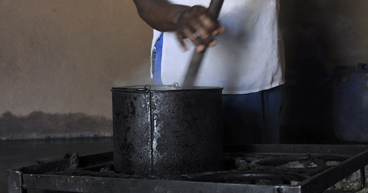 A woman cooks maize porridge at a farm near Harare, Zimbabwe.</p>